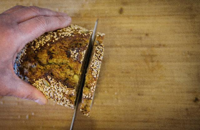 Brot wird auf Holzbrett geschnitten